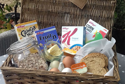 Brekfast hamper consisting of cereal, muesli, free range eggs, bread, butter, preserves, plus tea, coffee and hot chocolate